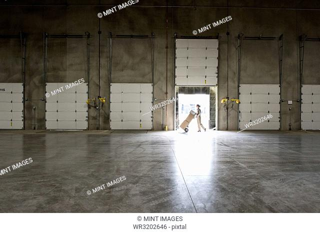 A warehouse worker with a hand truck walking past an open loading dock door in a large distribution warehouse