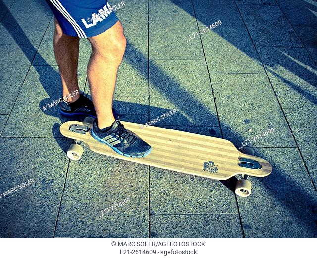 Detail of a skateboard and legs of its owner. Barcelona, Catalonia, Spain