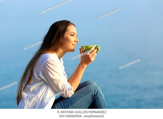 Side view portrait od a woman with a mug relaxing at sunset on the beach with a warm light