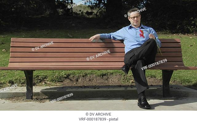A man sits alone on a park bench with two flowers