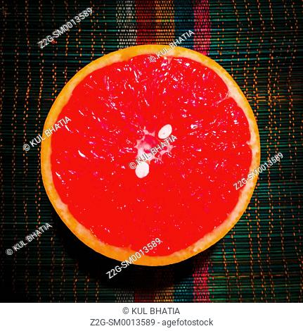 Half a grapefruit on a colourful bamboo mat, Ontario, Canada