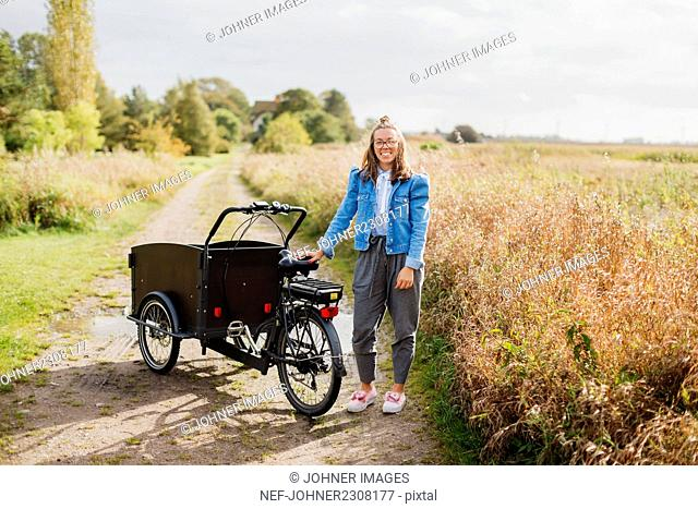 Woman standing near bicycle with cart
