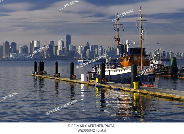 Police boat on Lonsdale Quay with Vancouver skyline coal cargo ship and Seabus ferry