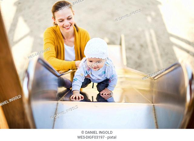 Baby girl climbing on shute on playground being held by her mother