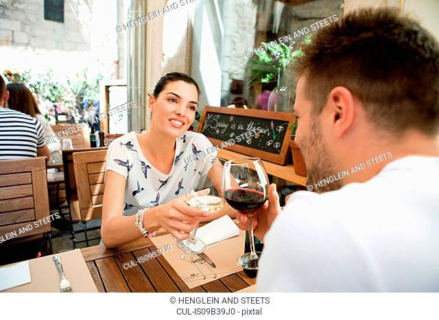 Young couple raising a wine toast at sidewalk restaurant, Split, Dalmatia, Croatia