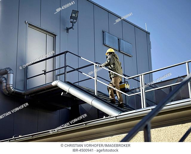 Engineer with yellow helmet and tool box using a staircase to an engine room, Austria