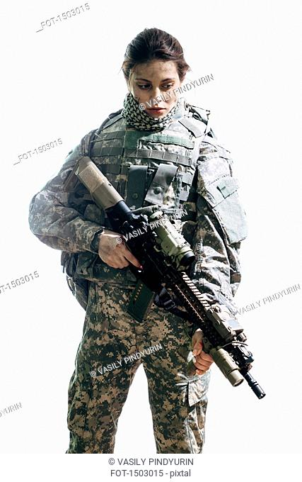 Thoughtful army soldier carrying rifle standing against white background