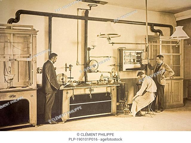 Early twentieth century archival photograph of scientist and police inspectors working in forensic laboratory looking for crime evidence