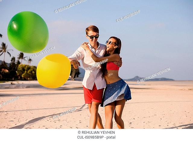 Young couple on beach playing with balloons, Koh Samui, Thailand
