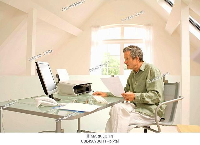 Senior man using computer and doing paperwork at home desk