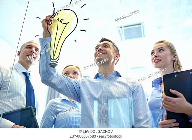 business, people, teamwork and planning concept - smiling business team with marker and light bulb doodle working in office