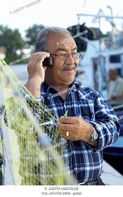 Mature fisherman fixing net while on cell phone