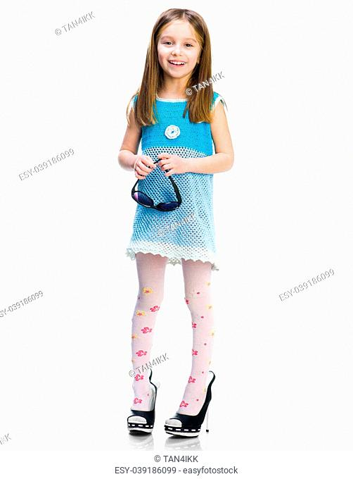 Pretty little girl in big shoes on a white background