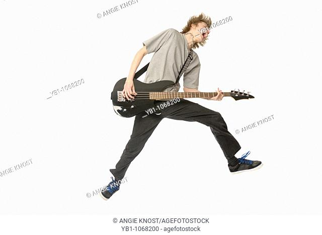 Teenage boy jumping in while playing bass guitar
