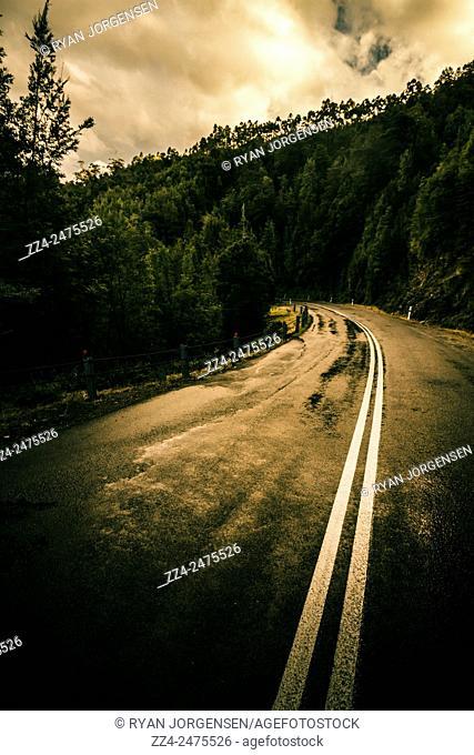 Wet highland road leading through a Tasmanian mountain range during stormy overcast day. Derwent Bridge, Australia