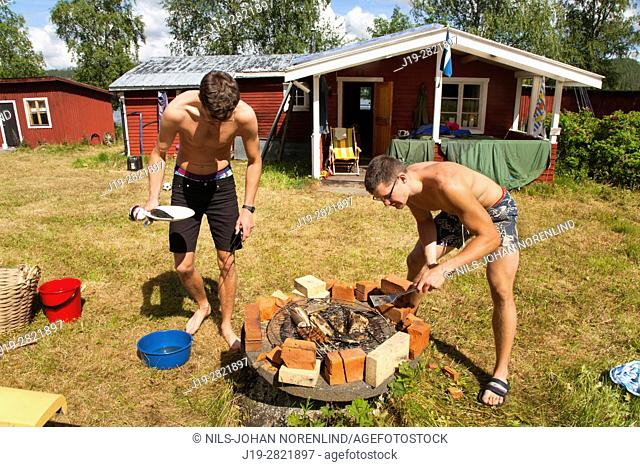 Brothers grilling fish, Northern Sweden