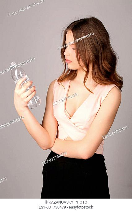 Girl viewing the bottle of water, high fashion look, healthy lifestyle, beautiful girl, smiling girl, isolated, perfect make-up, big lips, model in studio