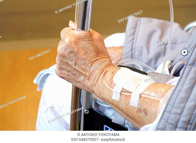 Close up of elderly woman hands with intravenous drip on a wheelchair