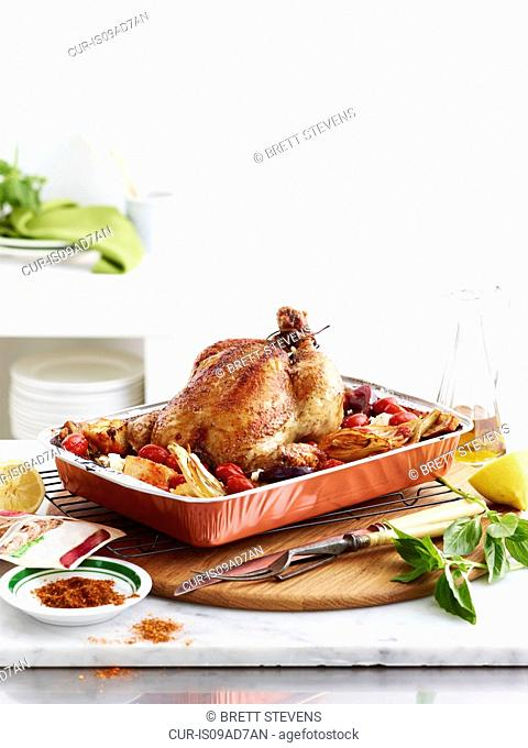 Roast chicken dish with vegetables, lemon and basil