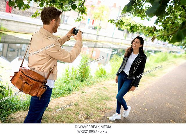 Man clicking picture of woman from digital camera
