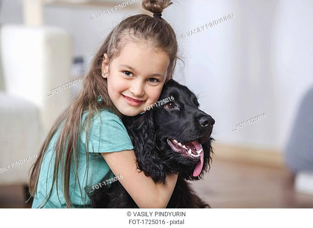 Portrait of smiling girl embracing Cocker Spaniel at home