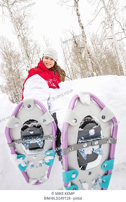 Portrait of smiling Caucasian girl wearing snowshoes
