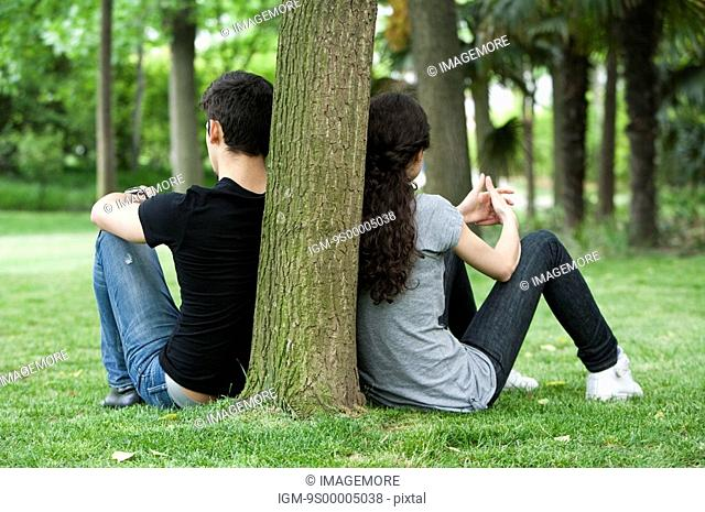Young couple leaning to a tree trunk back to back, sitting on lawn