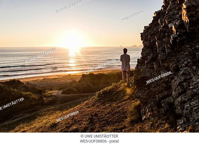 Back view of woman standing on cliff watching sunset