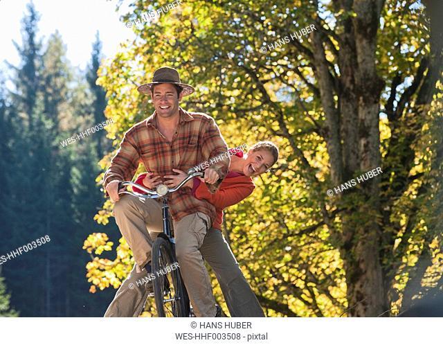 Austria, Salzburg, Flachau, Man and woman together having ride on bike