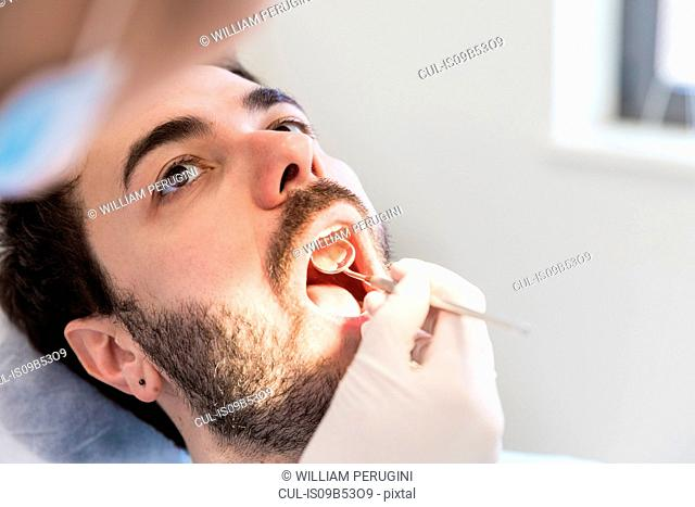 Close up of dentist giving male patient dental examination