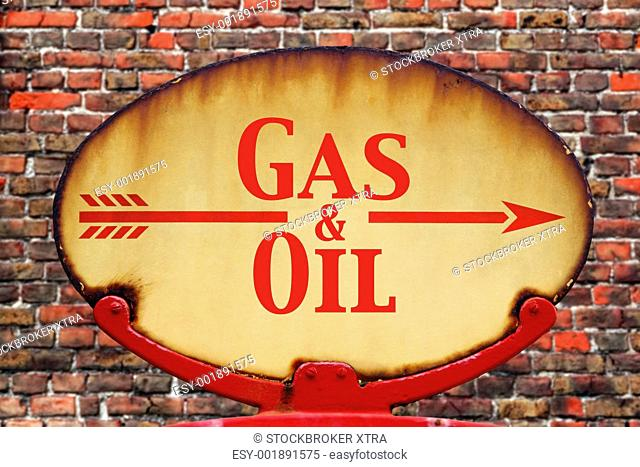 A rusty old retro arrow sign with the text Gas and Oil