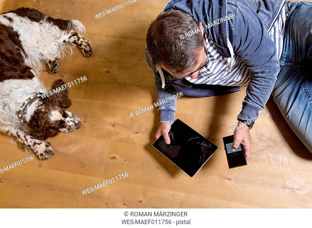 Overhead view of man using smartphone on the floor next to dog