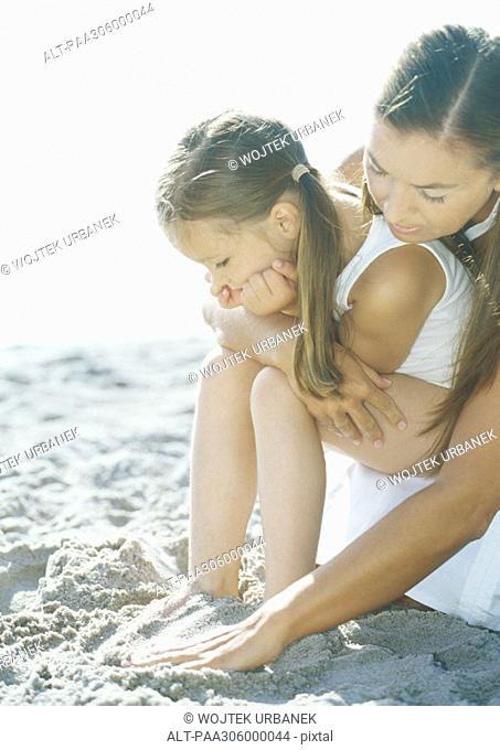 Girl sitting on mother's lap on beach