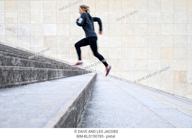 Blurred view of Caucasian woman running up staircase