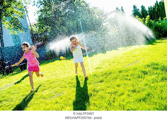 Children having fun with lawn sprinkler in the garden