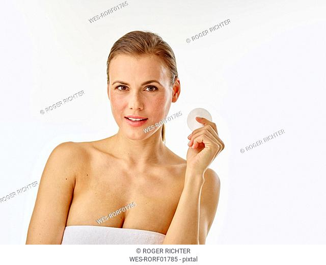 Young woman using cotton pad