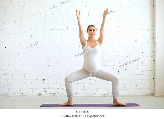 Pregnancy Yoga and Fitness concept. Portrait of beautiful young pregnant yoga model working out indoor. Pregnant happy fitness person enjoy yoga practice at...