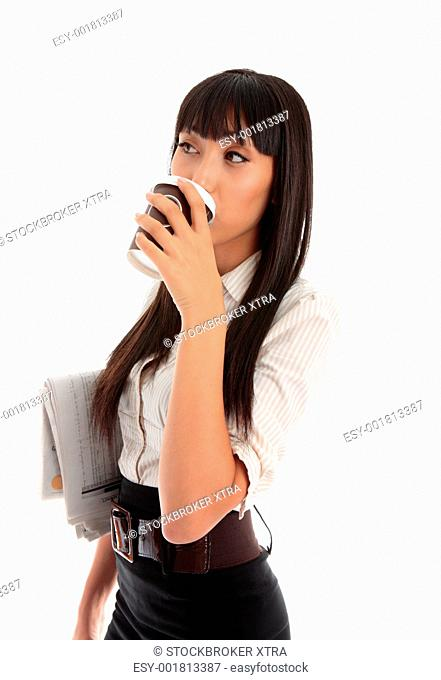 A professional young businesswoman drinking takeaway coffee and she has the financial newspaper under arm