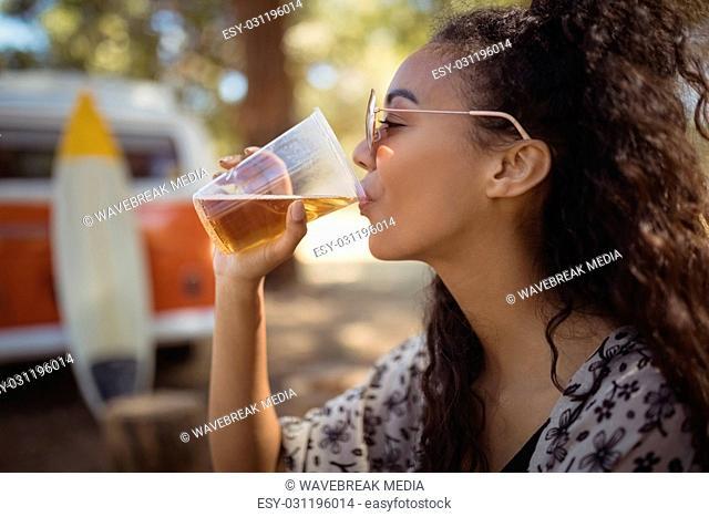 Woman drinking beer on field