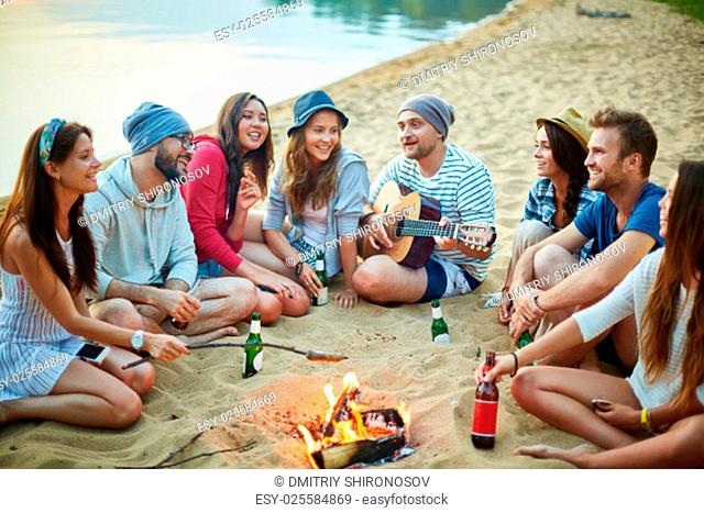 Young friends sitting around campfire and singing by guitar in the evening