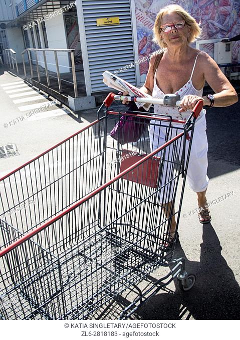 Mature retired senor caucasian woman putting back her empty cart after doing her grocery shopping on vacation