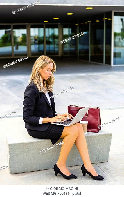 Businesswoman with fashionable leatherbag and coffee to go sitting on bench using laptop