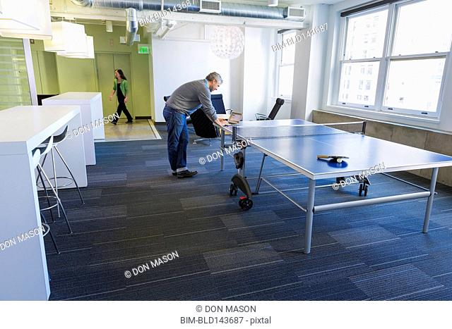 Businessman standing at table tennis table in office