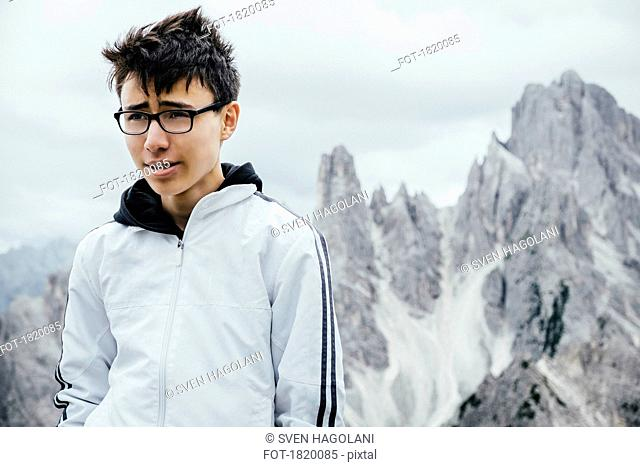 Teenage boy standing at rugged mountain peaks, Drei Zinnen Nature Park, South Tyrol, Italy