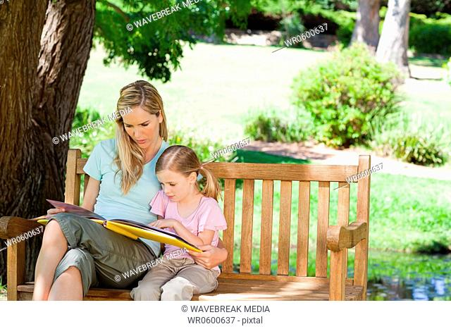 A mother and her daughter sit on the park bench and read