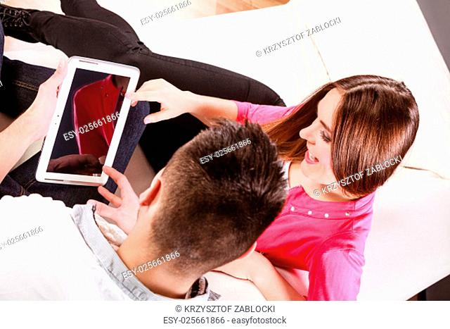 modern technologies leisure and relationships concept. young couple using a tablet pc computer sitting on a couch at home websurfing on the internet