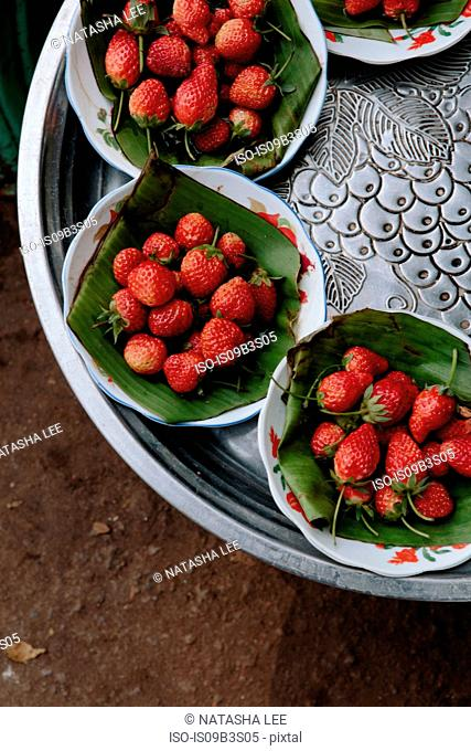 Overhead view of tray with bowls of fresh strawberries