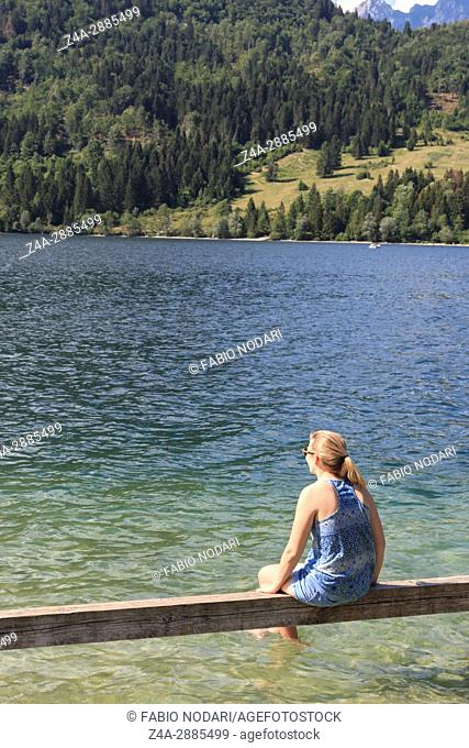 Tourist relaxing on a bench on lake Bohinj, a famous destination not far from lake Bled