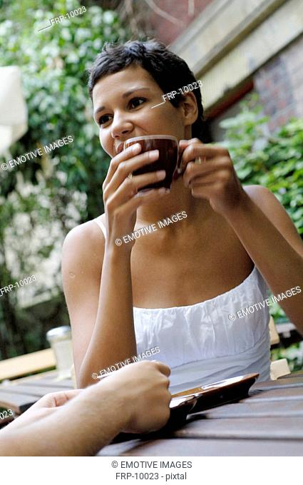 Young woman with cup of coffee outdoors
