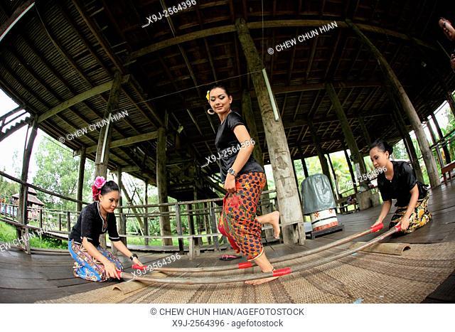 Dancer in traditional costume peforming bamboo dance in the Sarawak Cultural Village, Kuching, Sarawak, malaysia, borneo